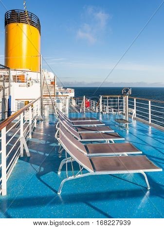 empty sunbathing chairs on upper deck of cruise liner in sunny day