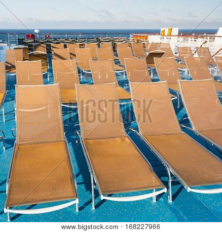 many empty sunbathing chairs on upper deck of cruise liner