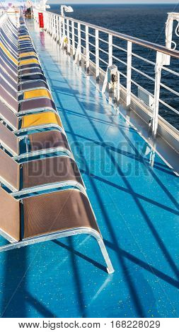 line of empty sunbathing chairs on deck of cruise liner