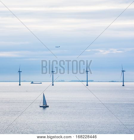 Travel to Denmark - view of boat ship airplane and offshore wind farm Middelgrunden in Oresund near Copenhagen city in Baltic Sea in blue autumn morning