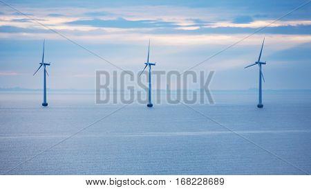 Travel to Denmark - turbines of offshore wind farm Middelgrunden in Oresund near Copenhagen city in Baltic Sea in blue autumn morning