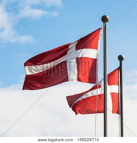 Travel to Denmark - two danish flags fluttering in wind in Copenhagen city in autumn day