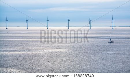 Travel to Denmark - calm surface of Baltic Sea with offshore wind farm Middelgrunden in Oresund near Copenhagen city in blue autumn morning
