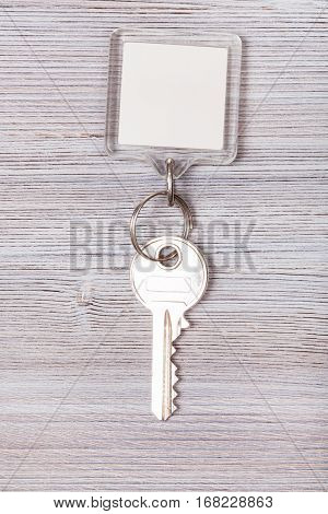 door key with white blank keychain on wood board