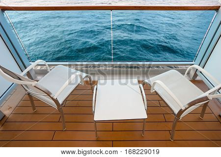 two empty chairs and table on board of cruise liner