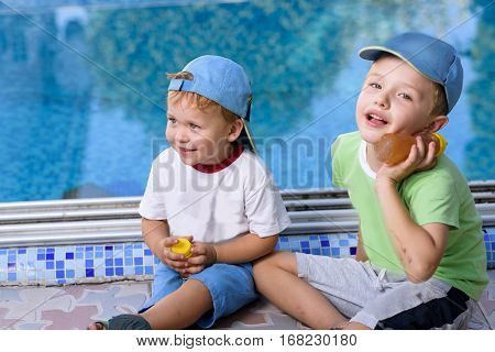 Two adorable sibling kids having fun outdoors. Cute brothers playing together with honey jar on sunny warm summer day. Brother love. Happy boys smiling on a sunny day by the pool. Brothers portrait