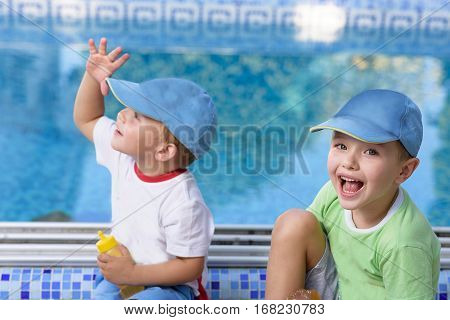 Two adorable sibling kids having fun outdoors. Cute brothers playing together on sunny warm summer day. Brother love. Happy boys smiling on a sunny day by the pool. Brothers portrait