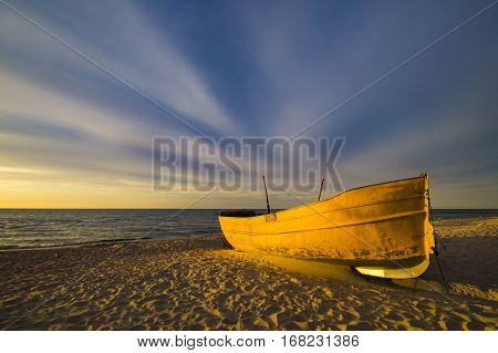 sunset over the sea beach,yelow boat,baltic sea,poland