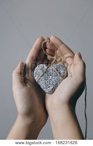 Hands holding a stone heart in jute bondage against grey background Valentine's day concept