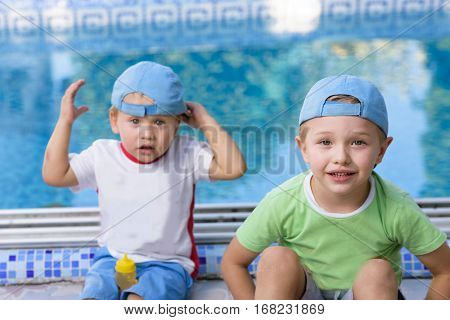 Two adorable siblings. Big brother not happy with his little brother. Cute kids playing together on sunny warm summer day. Brother love relationship