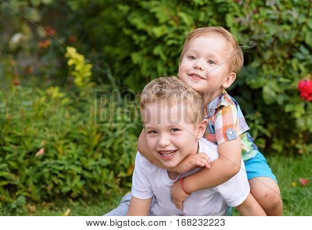 Two adorable brothers kids having fun outdoors. Cute siblings playing together on a sunny warm summer day. Family love. Happy boys smiling portrait