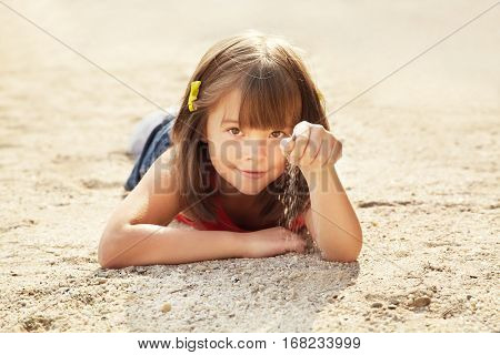 smiling cute little girl lying on the sand. child on vacation outdoor. sea beach