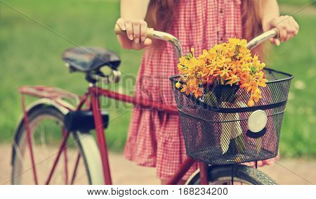 young woman with a bike in the park . flowers in a basket. Outdoors