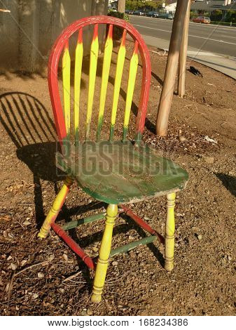 This is a handpainted side chair that is outdoors and painted in a folk art fashion in San Jose