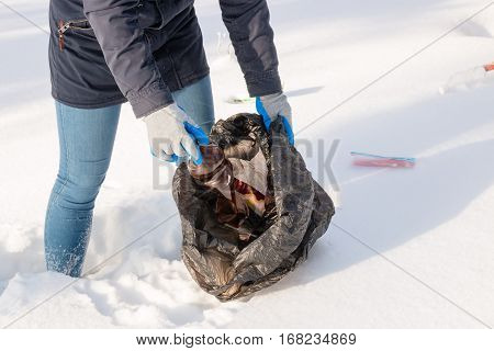Girl collects garbage in winter close up