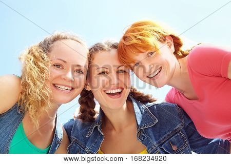Three happy girls looking at camera and laughing. girls embracing. vew from below
