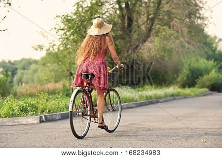 young woman in a dress and hat rides a bike in a summer park. Active people. Outdoors
