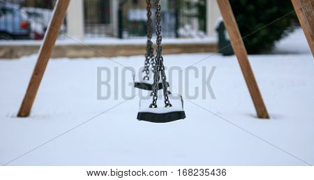 Wooden swing close up covered with snow
