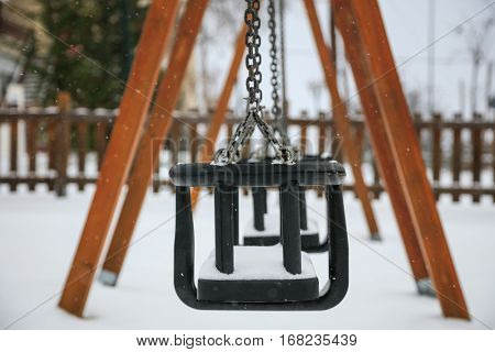 Wooden swing covered with snow