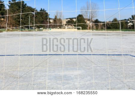 Empty soccerball field covered with snow