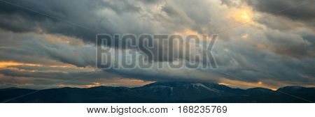 Heavy clouds over mountains at sunset