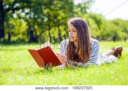 Portrait fo a gorgeous young brunette student outdoors reading book