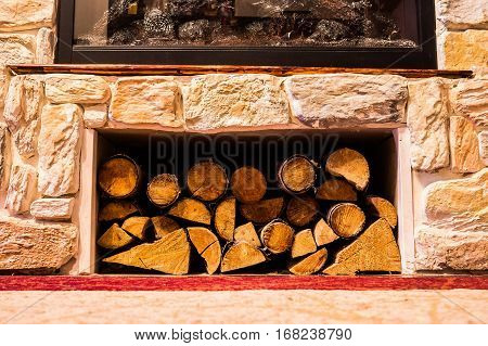 pile of small logs under a fireplace decorated with stone