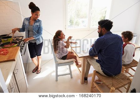 Dad helping kids with homework and mum cooks, elevated view