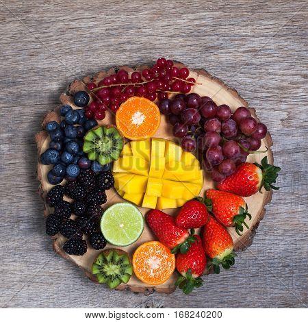 Raw fruit and berries platter mango kiwis strawberries blueberries blackberries red currants grapes top view square