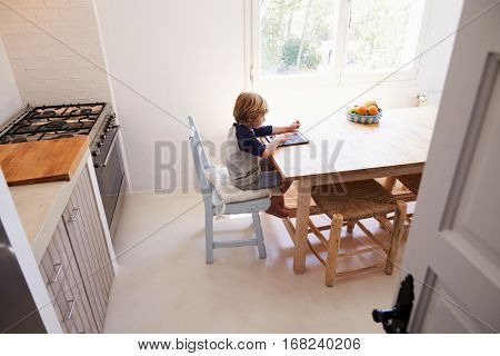 Boy using tablet in kitchen, elevated view from doorway