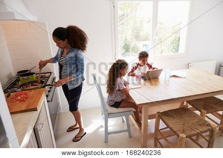 Mum cooking while kids work at kitchen table, elevated view