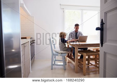 Dad and son using computers at kitchen table, from doorway