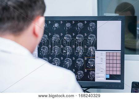 Doctors consider and discuss magnetic resonance image (MRI) of the brain. Back view selective focus