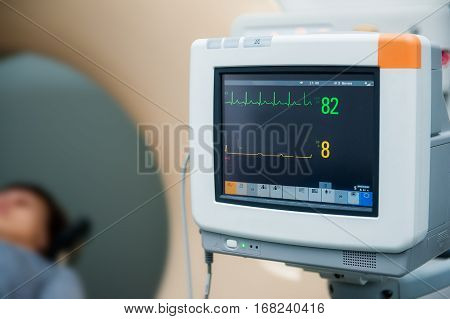 Close Up Electrocardiograph Showing Patient Heart Rate With Pacient Lying In Computed Tomography Roo
