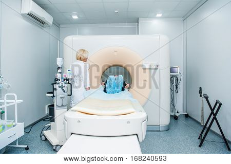 Female Doctor Adjusts Computed Tomography Or Computed Axial Tomography Scan Machine With Lying Patie