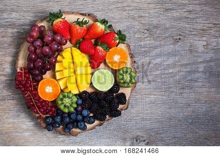 Raw fruit and berries platter mango kiwis strawberries blueberries blackberries red currants grapes top view copyspace for text