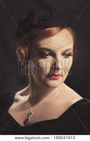 Twenties style portrait of glamorous woman wearing a pillar box hat