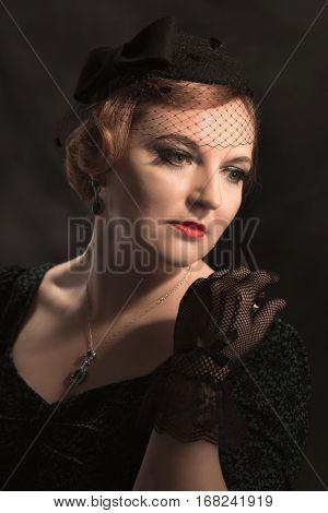 Glamorous twenties style portrait of woman wearing black lace gloves and pillar box hat