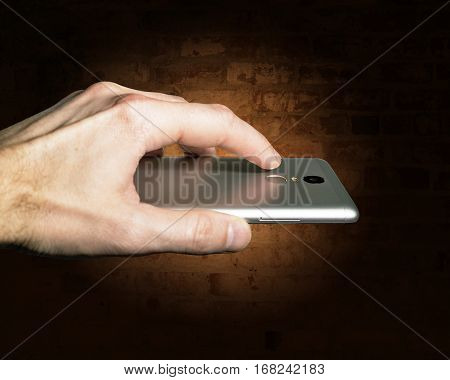 Finger touches the fingerprint scanner on the smartphone against a brick wall