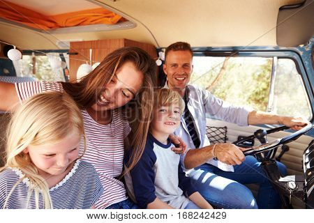 Family sitting at the front of their camper van, dad driving
