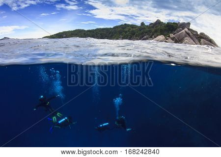 Scuba divers and island. Over under split image