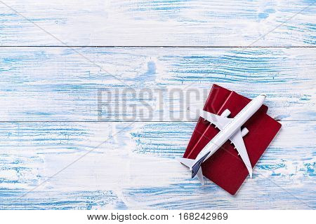 White Blank Model Of Passenger Plane And Passports On Blue Wooden Background