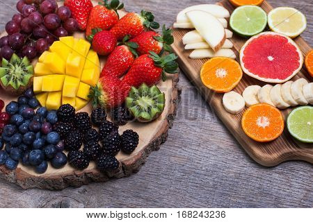 Raw fruit and berries platter mango kiwis strawberries blueberries blackberries red currants grapes