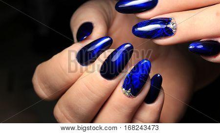 manicure design nails, blue gel polish with rhinestones cat eyes