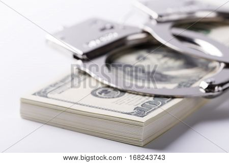 Pair Of Handcuffs Closeup On Dollar And Euro Banknotes Stacks