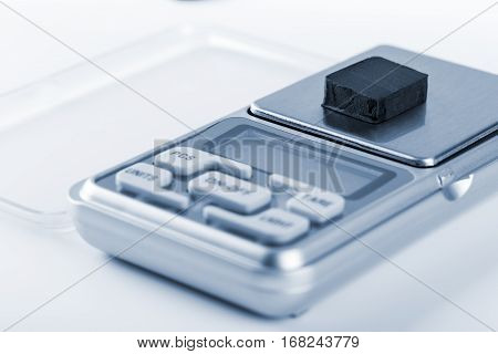 Block Of Hashish On Digital Scales Over White Background. Blue Tone