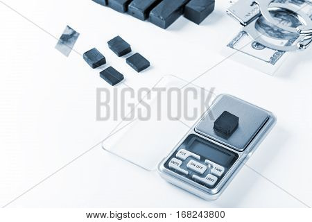 Blocks Of Hashish On Digital Scales Over White Background.  Blue Tone