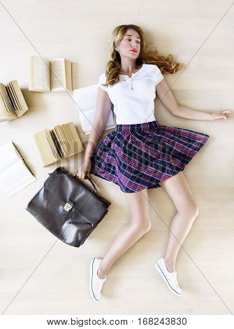 Girl going back to school. Pretty Teen Girl Student holding school bag and books with a sad expression. Top view