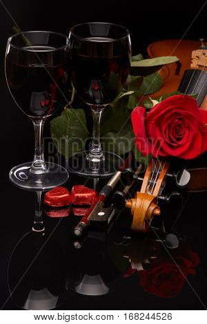 Violin (fiddle), red hearts, two glasses of wine and red rose on a black background. String instrument. Valentine's day.