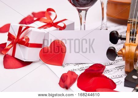 Violin (fiddle), notes, two glasses of red wine, petals of red rose and gift boxes on a white background. Empty bussiness card. Copy space for text.  Valentine's day.